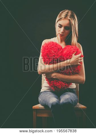 Broken heart love concept. Sad unhappy woman holding red heart pillow dark background