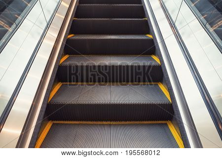 Escalator and step inside building, gray and black color.