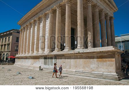 Nimes, France - July 04, 2016. View of the Maison Carrée with people, an ancient Roman temple in the city center of the ancient town of Nimes. In the Gard department, Occitanie region, southern France