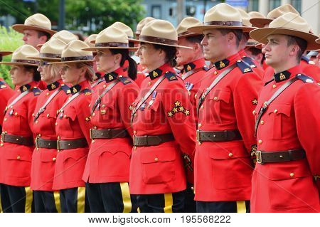 Victoria BC,Canada,June 10th 2014.Men and women RCMP police in their red uniforms stand at ease at a ceremony honoring fallen officers in Victoria BC.