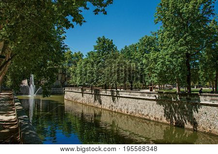 View of canal at the 18th-century Gardens of the Fountain, built around the Roman thermae ruins, in the city center of Nimes. Located in the Gard department, Occitanie region in southern France
