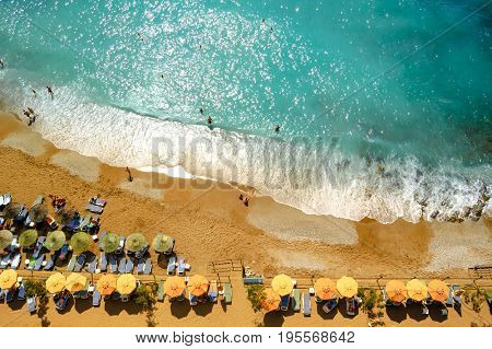 Aerial View of Beautiful Summer Beach with People, Warm Blue Sea and Umbrellas. Travel and Vacation Concept.