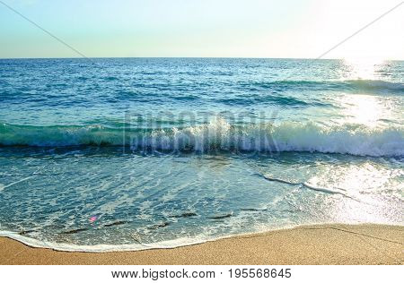 Beautiful Summer Seascape with Warm Waves of Blue Sea and Sand Beach in Sun Light. Travel and Vacation Concept.