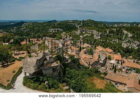 Baux-de-Provence, France - July 05, 2016. View of the Baux-de-Provence castle ruins on the hill, with roofs of the village just below. Bouches-du-Rhône department, Provence region, southeastern France
