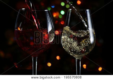 Beautiful splash of wine in a glass against the festive lights