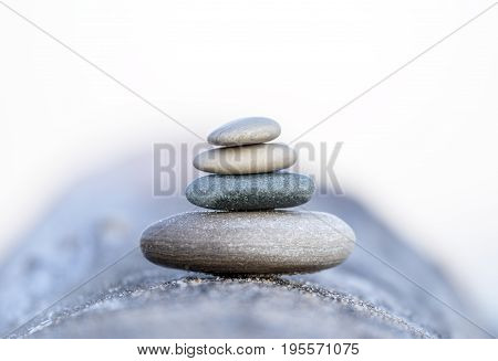 Four Smooth Beach Stones Stacked And Balanced On A Driftwood Log