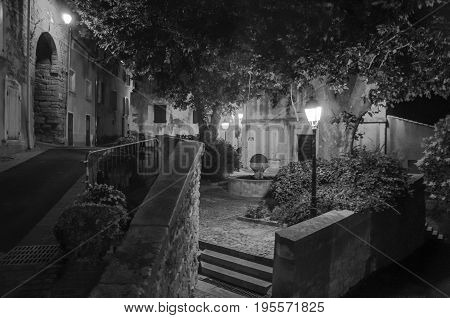 Châteauneuf-de-Gadagne, France - July 06, 2016. Night view of street and houses in the charming city center of Châteauneuf-de-Gadagne. In Vaucluse department, Provence region, southeastern France. Black&white image