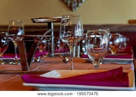 Glasses, Flowers, Fork, Knife Served For Dinner In Restaurant With Cozy