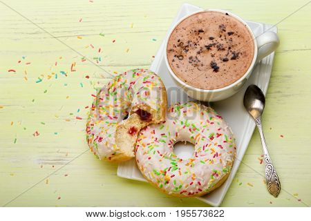 Cup of coffee and tasty donuts with icing and chocolate on green wooden background copy space