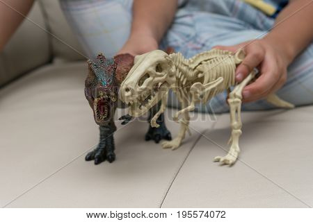 kids playing a tyrannosaurus toy and tyrannosaurus skeleton on a sofa at home