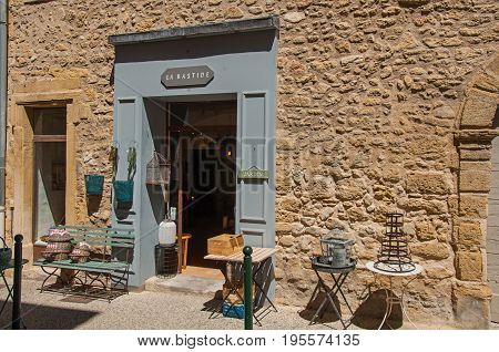 Lourmarin, France - July 07, 2016. Close-up of typical stone houses and shops on a street of the historical village of Lourmarin. Located in Vaucluse department, Provence region, southeastern France
