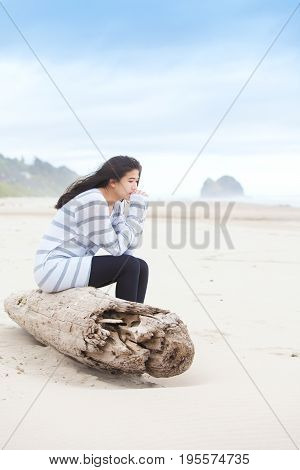 Biracial Asian Caucasian teen girl sitting on large driftwood log on beach looking out towards ocean on cloudy day