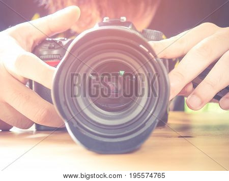 Photography or traveller Concept.The photographer hold black DSRL camera in his hands with sunlight in summer season selective focus. Photo of Vintage style and filtered process.