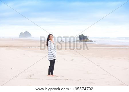Beautiful biracial teen girl standing on sandy beach by ocean happily smiling and enjoying the outdoors