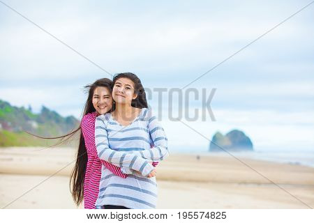 Two biracial Asian Caucasian teen girls hugging laughing smiling and enjoying the beach together