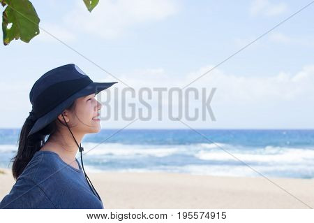 Biracial teen girl wearing hat looking out over beautiful blue ocean side profile smiling