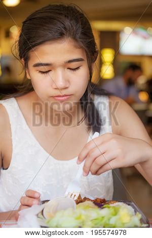 Biracial teen girl smiling eating shrimp with chopsticks in restaurant