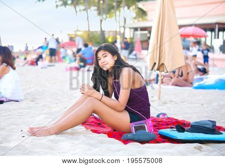 Biracial teen girl sitting on crowded Hawaiian beach relaxing