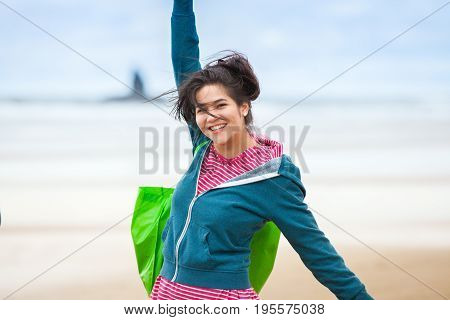 Smiling biracial Asian Caucasian teen girl in blue hoodie jacket standing on beach outdoors arms stretched out over head