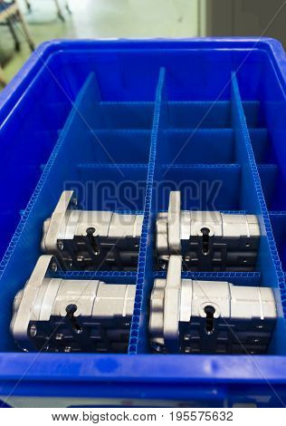 Automotive Aluminium parts kept in a blue plateic box ; parts produced by Low Pressure Die casting process and cnc machining machine