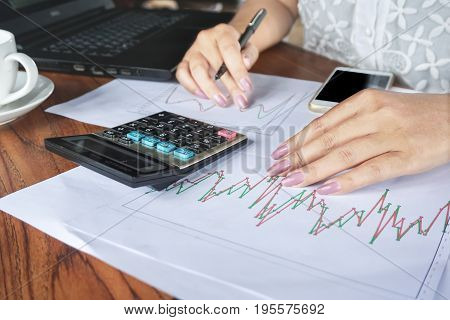 businesswoman hand analyzing stock,financial graph report with calculator,smart phone and notebook on wooden office desk