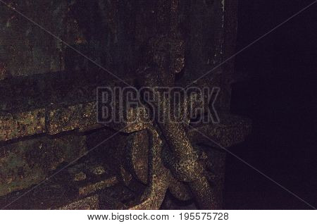Old terrible rusty door from the bomb shelter in a completely dark dungeon. Vintage action.