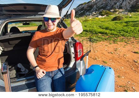 Summer, holiday, trip and vacation concept - Man near the car showing thumbs up and ready to travel.
