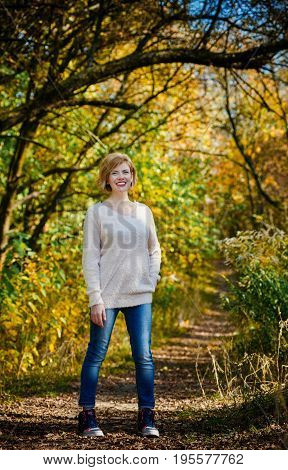 Happy excited young woman in autumn forest