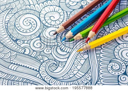 Colored wooden pencils close-up on a coloring background