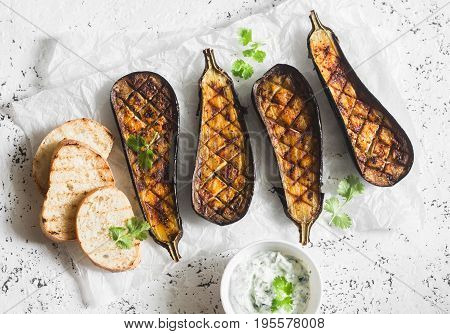 Grilled eggplant and sauce tzatziki on a light background top view. Baked aubergine