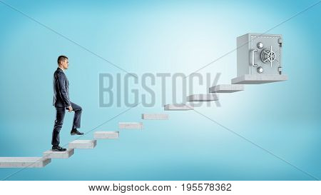 A businessman on blue background going upstairs to a large metal safe box on concrete blocks. Banking business. Safety and insurance. Save money.