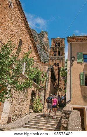 Moustiers-Sainte-Marie, France - July 08, 2016. People and staircase and belfry in an alley in the lovely village of Moustiers-Sainte-Marie. Provence region, southeastern France