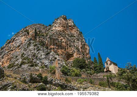 View of the Notre-Dame de Beauvoir church amidst cliffs and rock stairway, above the graceful Moustiers-Sainte-Marie village. Alpes-de-Haute-Provence department, Provence region, southeastern France