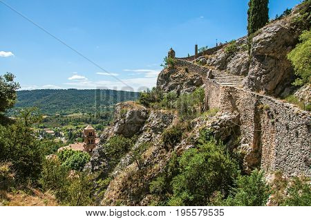 View of the path to the Notre-Dame de Beauvoir church with the graceful village Moustiers-Sainte-Marie underneath. Alpes-de-Haute-Provence department, Provence region, southeastern France