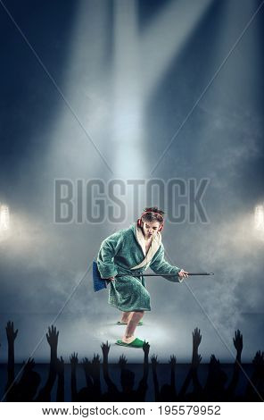 Young man wearing dressing gown pretending to play guitar with the broom and listening music to headphones imagine that he is playing on stage in front of an audience.