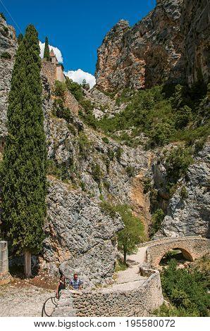 Moustiers-Sainte-Marie, France - July 08, 2016. Notre-Dame de Beauvoir church amidst cliffs and rock bridge, above Moustiers-Sainte-Marie. Provence region, southeastern France