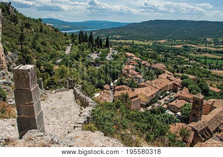 View of stone staircase, roofs and belfry under sunny blue sky in the charming village of Moustiers-Sainte-Marie. Located in Alpes-de-Haute-Provence department, Provence region, southeastern France