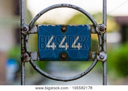 Plate with numbers 444 on the old fence.