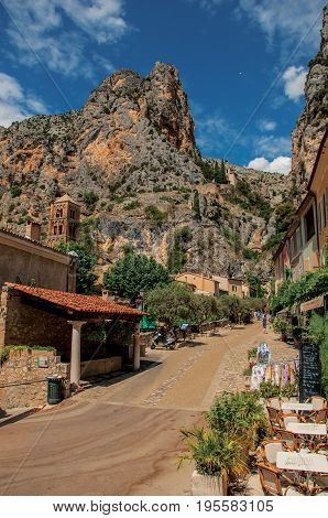 Moustiers-Sainte-Marie, France - July 08, 2016. Sunny street with shops and restaurants in the lovely village of Moustiers-Sainte-Marie. Provence region, southeastern France