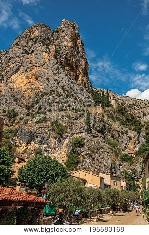 Moustiers-Sainte-Marie, France - July 08, 2016. Street with cliffs, shops and restaurants in the lovely village of Moustiers-Sainte-Marie. Provence region, southeastern France