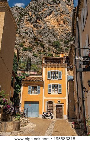 Moustiers-Sainte-Marie, France - July 08, 2016. Sunny street with houses and motorbike in the lovely village of Moustiers-Sainte-Marie. Provence region, southeastern France