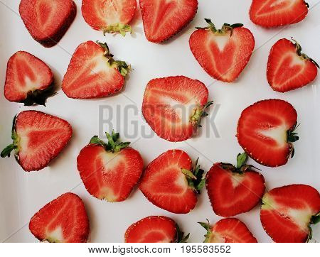Strawberry creative pattern. Isolated food backdrop. Sliced ripe red berry with green leaves on white background.