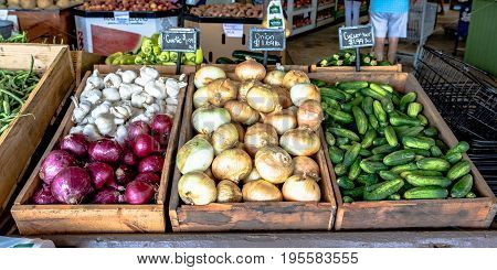 Display of onions garlic and cucumbers at a roadside produce stand.
