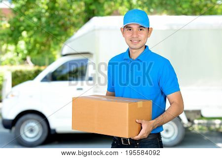 Deliveryman carrying a cardboard parcel box in front of delivery car