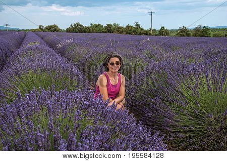Valensole, France - July 08, 2016. Woman in lavender field smiling, near the village of Valensole. Located in the Alpes-de-Haute-Provence department, Provence region, in southeastern France