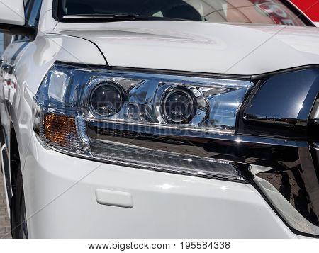 Car headlight of a new white car with chrome trim.
