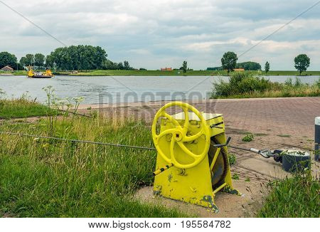 Yellow painted winch of a cable ferry sailing back and forth on a Dutch river.