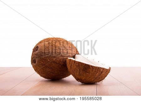 Whole and cut tropical brown coconuts on a light wooden table, isolated on a white background. Fresh tasteful cocos full of vitamins.