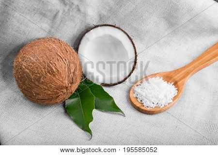 Fresh whole and crushed coconuts, light brown wooden spoon with juicy nut chips and bright green leaves on a gray fabric. Tropical coconuts with leaves. Coconut chips or flakes.