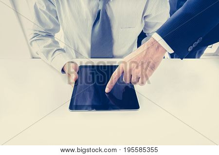 Two businessmen using tablet computer with one hand touching screen business discussion concept - vintage tone